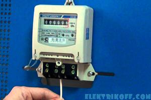 Электрик производит замену электросчетчика